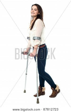 Full Length Portrait Of Young Girl Walking With Crutches