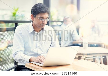 Candid Asian Indian man using laptop computer at outdoor cafe.