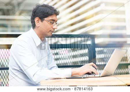Candid Asian Indian businessman using laptop computer, modern building at background.