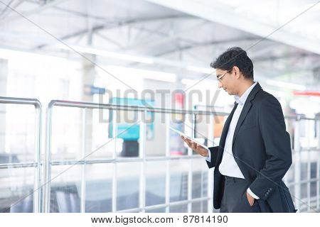 Asian Indian businessman using tablet pc while waiting train at railway station.