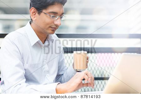 Asian Indian businessman using laptop computer while drinking a cup hot milk tea, outdoor cafe.