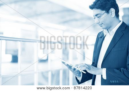 Asian Indian businessman using tablet pc while waiting train at railway station, blue toned.
