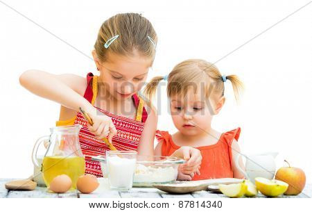 two little sisters cooking isolated on a white background