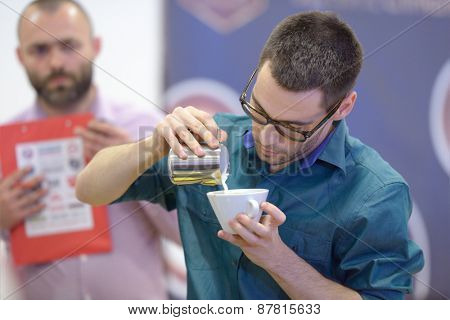 DNEPROPETROVSK, UKRAINE - MAY 30, 2013: Barista Sergey Merkulov in free pouring competition during 5th Ukrainian Latte Art Championship in Dnepropetrovsk, Ukraine on May 30, 2013