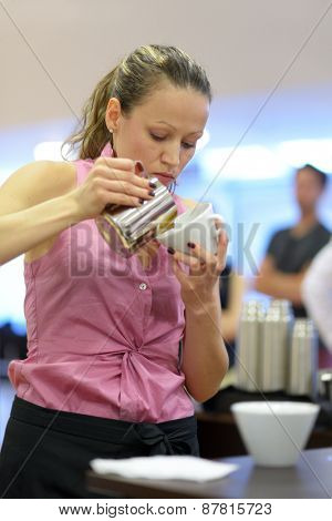 DNEPROPETROVSK, UKRAINE - MAY 30, 2013: Barista Lina Bayasan  in free pouring competition during the 5th Ukrainian Latte Art Championship in Dnepropetrovsk, Ukraine on May 30, 2013