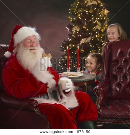 Santa Eating Cookie With Two Little Girls Hiding