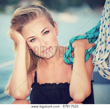 Closeup portrait of beautiful calm serious girl sitting down on sailboat and holding rope, relaxation in the sea, active summer vacation on luxury water transport