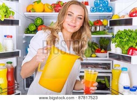 Happy woman standing near open refrigerator full of fresh fruits and vegetables and pouring juice in glass, healthy eating concept