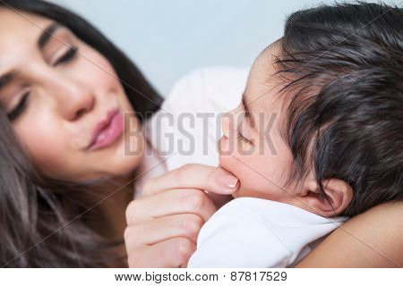 Closeup portrait of happy young mother touching face of her adorable little child, enjoying motherhood, family love concept