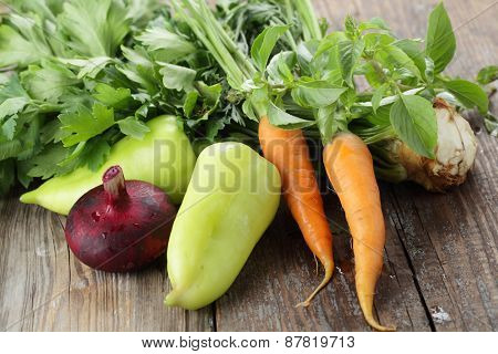 Red onion, green pepper, carrot, basil, and celery on a rustic table