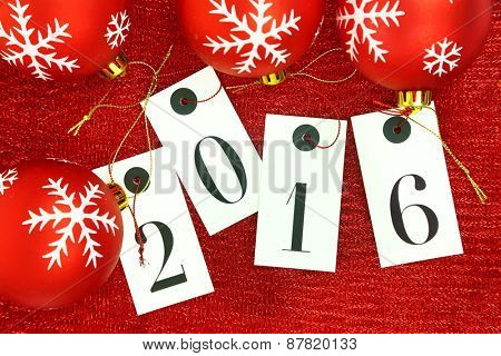 New year 2016 on tags and Christmas balls on red background