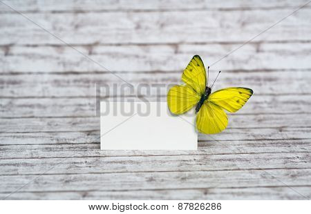 Small Blank White Card with Yellow Green Butterfly on Upper Right Corner, Emphasizing Copy Space, Placed on the Wooden Table.