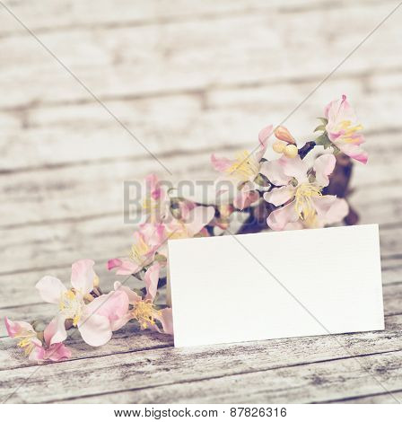 Close up Blank Small White Card with Attractive Orchids on a Stem on Top of a Wooden Table, Emphasizing Copy Space.