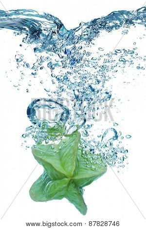 Bubbles forming in blue water after carambola is dropped into it.