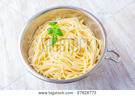 Cooked Pasta In The Strainer On White Wooden Table