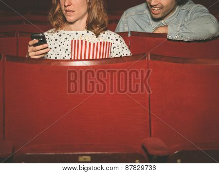 Woman Using Her Phone In Theater