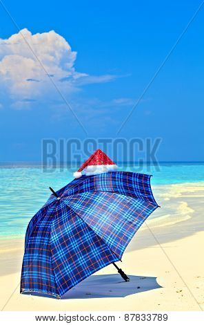 Blue Umbrella Is On A Beach With Santa Hat