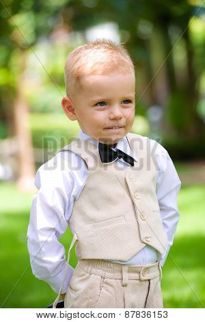 handsome little boy in a suit in park