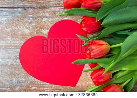 flowers, advertisement, valentines day and holidays concept - close up of red tulips and blank paper heart shape on wooden background