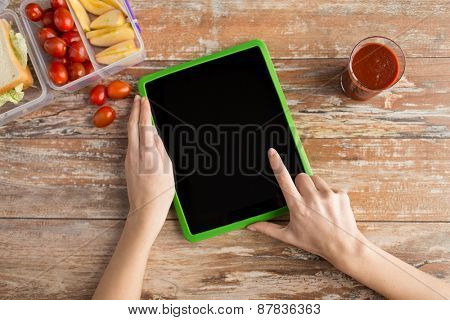healthy eating, dieting, technology and people concept - close up of woman hands with blank tablet pc computer and food in plastic container on table at home