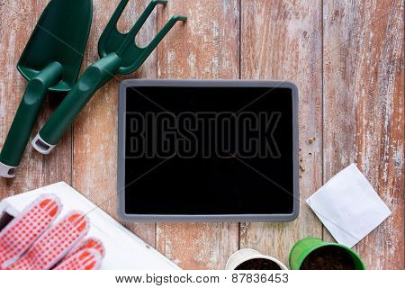 gardening, technology and planting concept - close up of tablet pc computer blank screen, seeds and garden tools on table