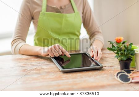 people, gardening, flowers and profession concept - close up of woman or gardener with tablet pc computer at home