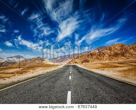 Travel forward concept background - road in mountains Himalayas with dramatic clouds on blue sky. Ladakh, Jammu and Kashmir, India