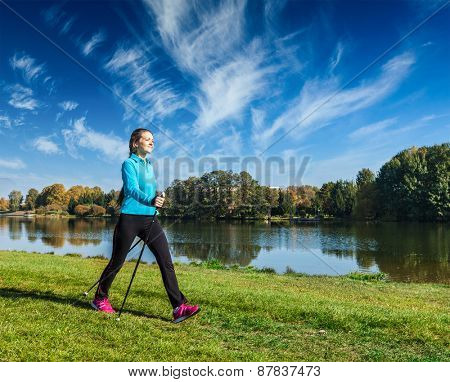 Nordic walking adventure and exercising - young woman hiking with nordic walking poles in park along river