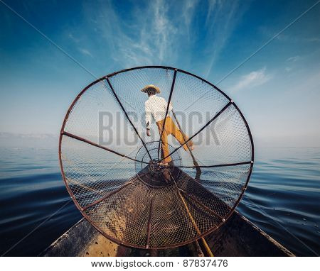 Myanmar travel attraction - Traditional Burmese fisherman with fishing net at Inle lake in Myanmar, view from boat. Vintage filtered retro effect image
