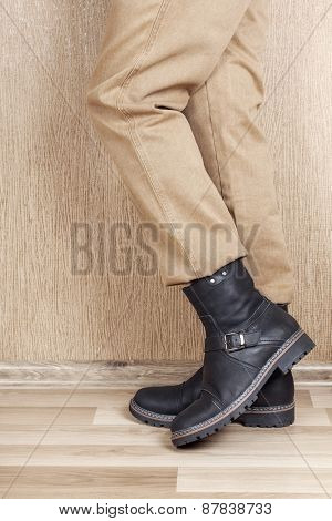 Men's leather shoes and jeans khaki legs. A man stands on a wooden floor near the wall.