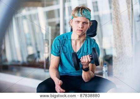 Teenager In The Gym Working With Dumbbells