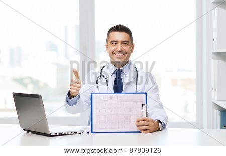 medicine, profession, technology and people concept - happy male doctor with clipboard and laptop computer showing thumbs up in medical office