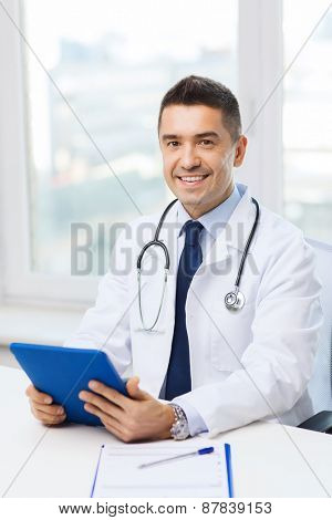 healthcare, profession, people and medicine concept - smiling male doctor in white coat with tablet pc in medical office
