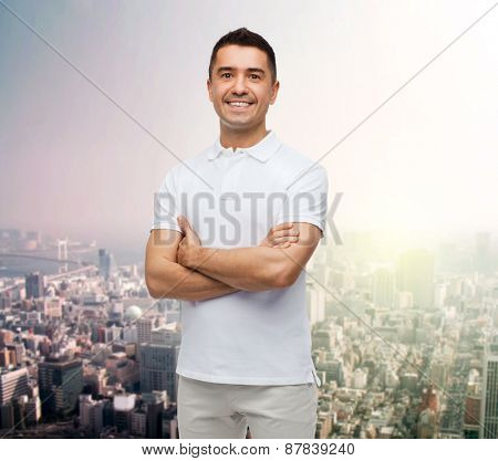 happiness and people concept - smiling man in white t-shirt with crossed arms over city background