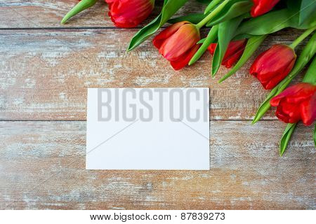 advertisement, valentines day, greeting and holidays concept - close up of red tulips and blank paper or letter on wooden background