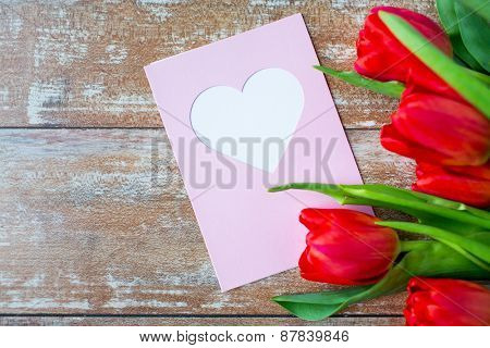 valentines day, greeting, love and holidays concept - close up of red tulips and greeting card with heart