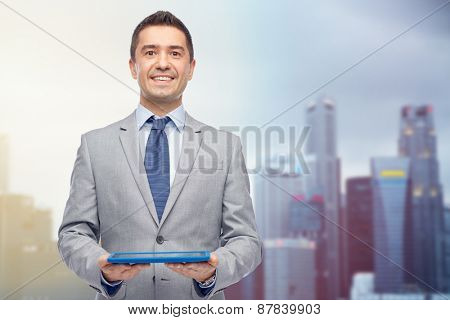 business, people and technology concept - happy smiling businessman in suit holding tablet pc computer over city background