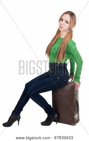 Attractive red-haired woman on old suitcase