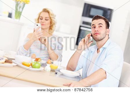 A picture of a young couple eating breakfast in the kitchen and using smart phone