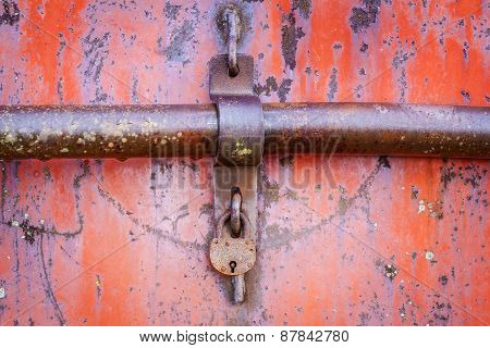 Old rusted padlock on red metal door