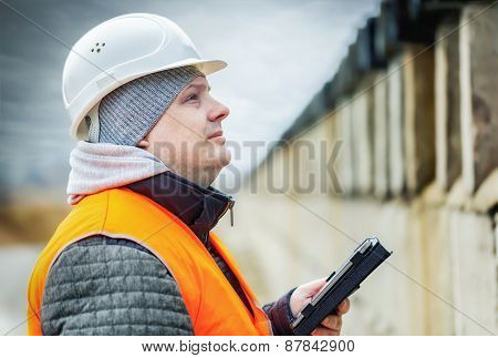 Engineer with tablet PC near the concrete wall