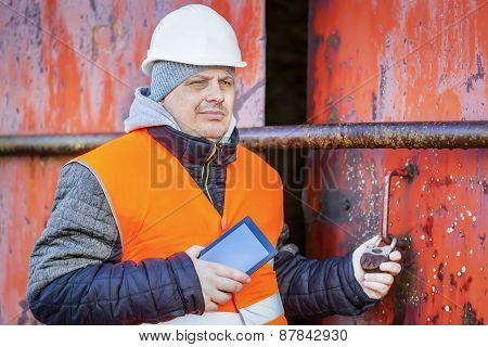 Worker with tablet PC near the red metal hangar door