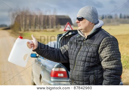 Man with empty can waiting for help near car