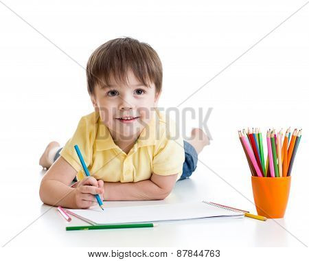 Cute child boy drawing with pencils in preschool isolated