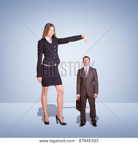 Smiling Young Businesswoman Pointing to small Businessman.