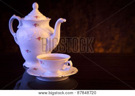Old-style Kettle With Cup Of Tea On Black