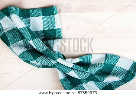 Green Folded Tablecloth Over Bleached Wooden Table