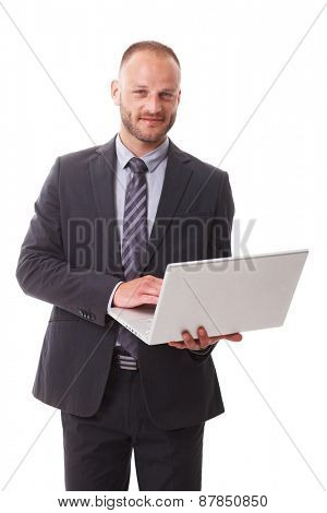 Businessman holding laptop in hand, working, smiling, looking at camera.