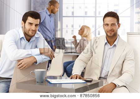 Portrait of handsome young businessmen sitting by table, looking at camera, smiling.