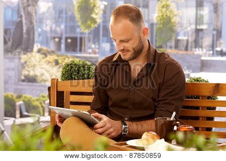 Casual man sitting in outdoor cafe on a bench, using tablet computer.